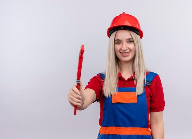 Lächelndes junges blondes ingenieur-baumeistermädchen in uniform in zahnspangen, die rohrschlüssel auf isoliertem leerraum mit kopienraum ausstrecken