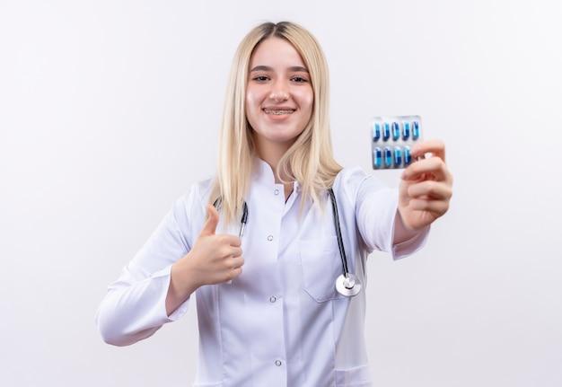Lächelndes junges blondes mädchen des doktors, das stethoskop und medizinisches kleid in zahnspange hält, die pillen ihren daumen auf lokalisiertem weißem hintergrund hält