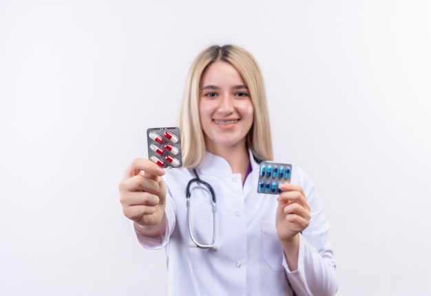 Lächelndes junges blondes mädchen des doktors, das stethoskop und medizinisches kleid in zahnspange hält, die pillen mit beiden händen auf lokalisiertem weißem hintergrund hält