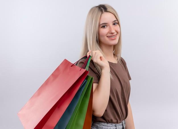 Lächelndes junges blondes mädchen in zahnspangen, die einkaufstaschen auf schulter auf lokalisiertem weißem raum halten