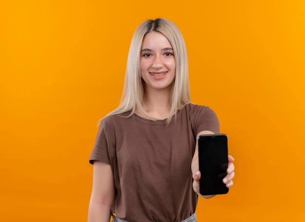 Lächelndes junges blondes mädchen in zahnspangen, die handy auf isoliertem orange raum mit kopienraum ausstrecken