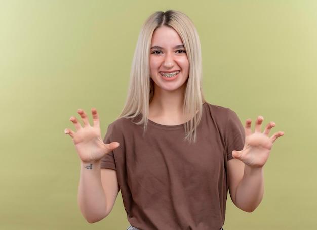 Lächelndes junges blondes mädchen in zahnspangen, die tigerpfoten gestikulieren auf lokalisierten grünflächen