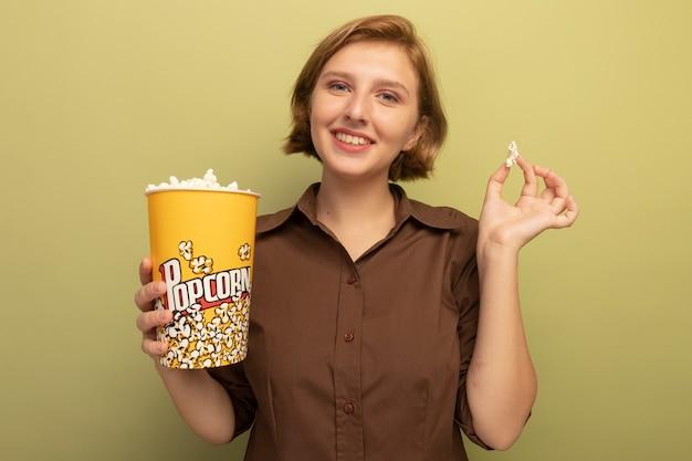 Lächelndes junges blondes mädchen mit eimer popcorn und popcornstück isoliert auf olivgrüner wand