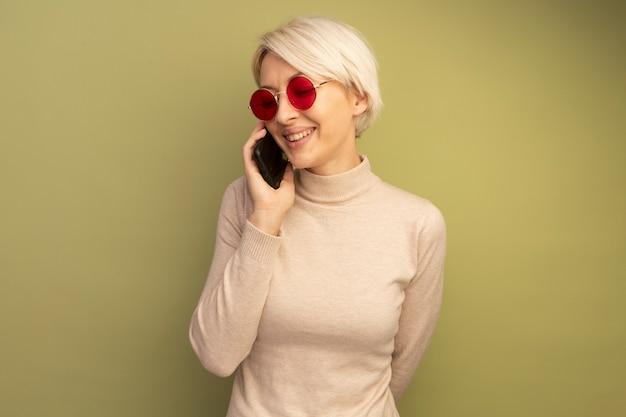 Lächelndes junges blondes mädchen mit sonnenbrille, das die hand hinter dem rücken hält und am telefon spricht und nach unten schaut
