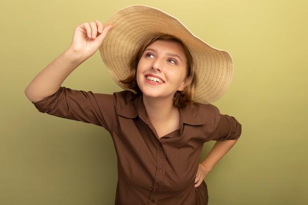 Lächelndes junges blondes mädchen mit strandhut, das den hut greift und die hand auf der taille hält und die seite isoliert auf olivgrüner wand mit kopienraum betrachtet