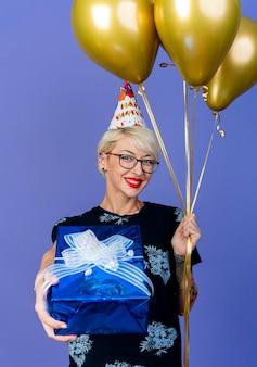 Lächelndes junges blondes partei-mädchen, das brille und geburtstagskappe hält, die ballons hält und geschenkbox in richtung kamera ausdehnt, die kamera lokalisiert auf lila hintergrund betrachtet