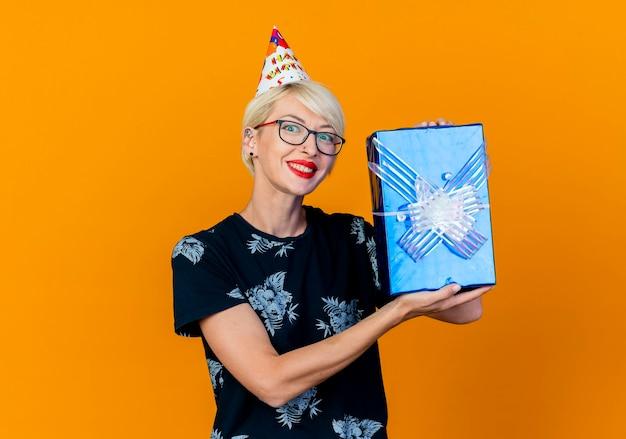 Lächelndes junges blondes partei-mädchen, das brille und geburtstagskappe trägt, die kamera zeigt geschenkbox lokalisiert auf orange hintergrund mit kopienraum