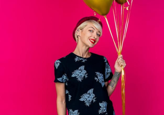 Lächelndes junges blondes partei-mädchen, das parteihut hält, der ballons hält, die kamera lokal auf purpurrotem hintergrund mit kopienraum betrachten