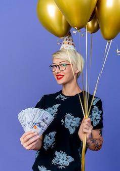 Lächelndes junges blondes parteimädchen, das brille und geburtstagskappe hält, die ballons und geld hält, die kamera lokalisiert auf lila hintergrund betrachten
