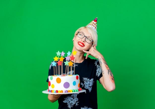 Lächelndes junges blondes parteimädchen, das brille und geburtstagskappe hält, die geburtstagstorte mit sternen betrachtet, die seite betrachten, die anrufgeste lokalisiert auf grünem hintergrund mit kopienraum tut