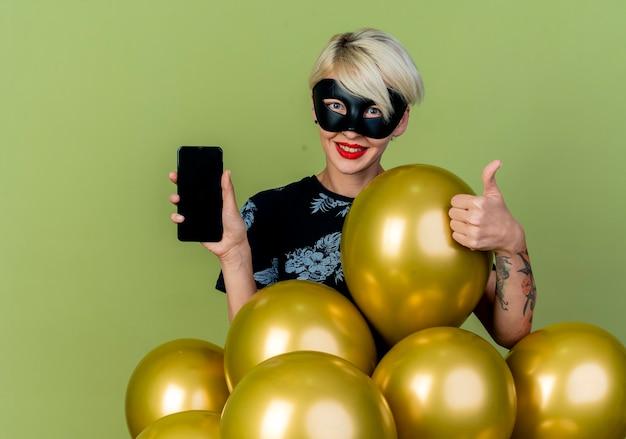 Lächelndes junges blondes parteimädchen, das maskerademaske trägt, die hinter luftballons steht, die handy und daumen oben betrachten kamera betrachten, die auf olivgrünem hintergrund mit kopienraum lokalisiert wird