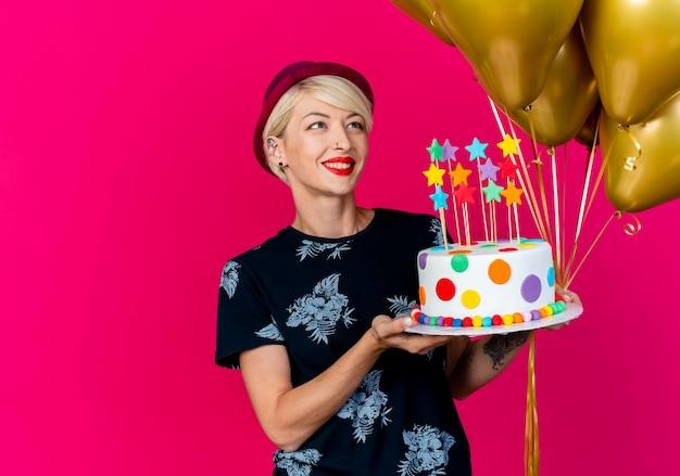 Lächelndes junges blondes partygirl, das partyhut hält, der ballons und geburtstagstorte mit sternen hält, die ballons lokalisiert auf purpurrotem hintergrund mit kopienraum betrachten