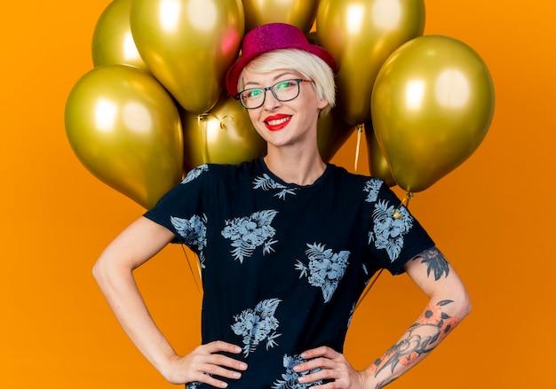 Lächelndes junges blondes partygirl, das partyhut und -brille trägt, die vor ballons stehen, die hände auf taille halten betrachten kamera lokalisiert auf orange hintergrund