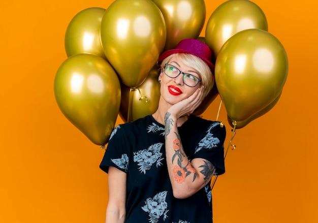 Lächelndes junges blondes partygirl, das partyhut und brille trägt, die vor ballons steht, die gesicht betrachten, das seite lokalisiert auf orange hintergrund betrachtet
