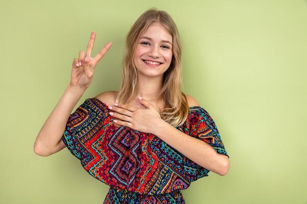 Lächelndes junges blondes slawisches mädchen, das hand auf ihre brust legt und victory-zeichen gestikuliert