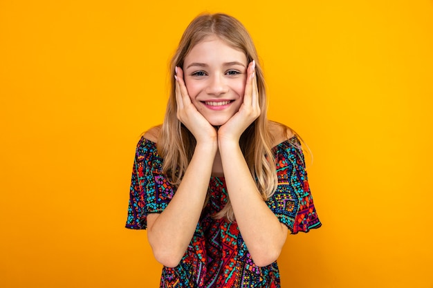 Lächelndes junges blondes slawisches mädchen, das sich die hände aufs gesicht legt und nach vorne schaut