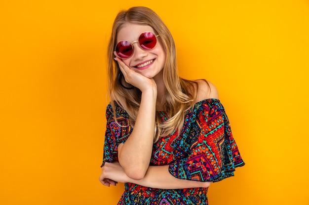 Lächelndes junges blondes slawisches mädchen mit sonnenbrille, das ihr die hand aufs gesicht legt und