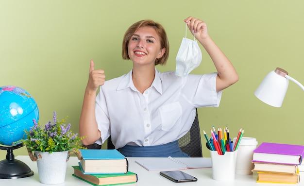 Lächelndes junges blondes studentenmädchen, das am schreibtisch mit schulwerkzeugen sitzt und eine schutzmaske hält und in die kamera schaut, die den daumen isoliert auf der olivgrünen wand zeigt