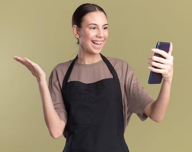 Lächelndes junges brünettes friseurmädchen in uniform hält die hand offen, hält und schaut auf das telefon