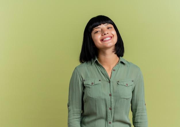 Lächelndes junges brünettes kaukasisches mädchen betrachtet kamera lokalisiert auf olivgrünem hintergrund mit kopienraum