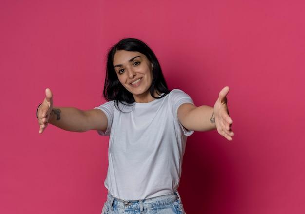 Lächelndes junges brünettes kaukasisches mädchen, das hände ausstreckt, die vorgeben, etwas isoliert auf rosa wand zu halten