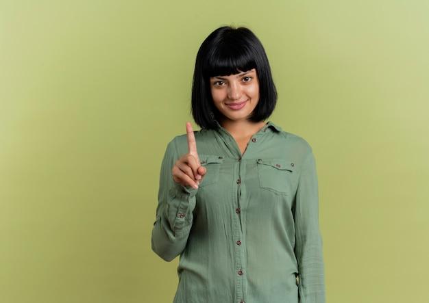 Lächelndes junges brünettes kaukasisches mädchen zeigt zeigefinger, der kamera lokalisiert auf olivgrünem hintergrund mit kopienraum betrachtet