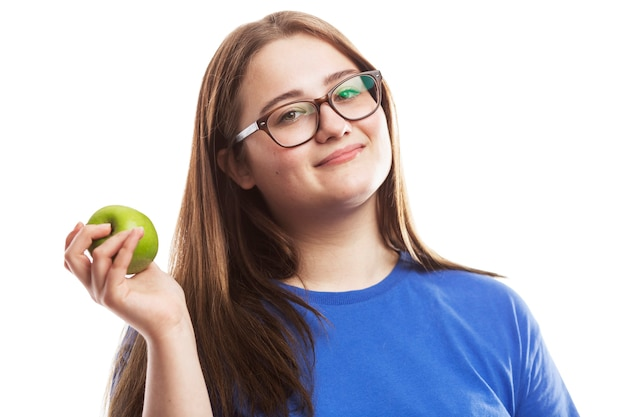 Lächelndes junges brünettes mädchen in den gläsern mit einem grünen apfel in ihrer hand. gesunde ernährung und vitamine. auf weißer wand isoliert.