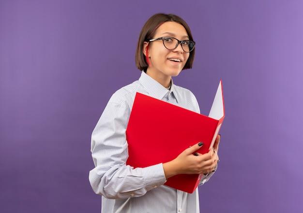 Lächelndes junges callcenter-mädchen, das brillen hält ordner isoliert auf lila wand