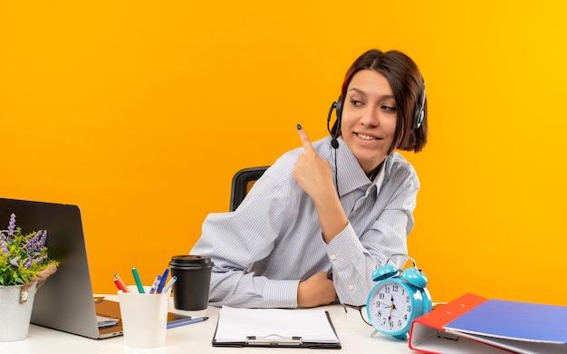 Lächelndes junges callcenter-mädchen, das headset trägt, sitzt am schreibtisch und schaut auf die seite, die hinter lokalisiert auf orange wand zeigt