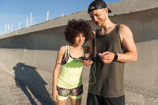 Lächelndes junges fitnesspaar, das musik hört