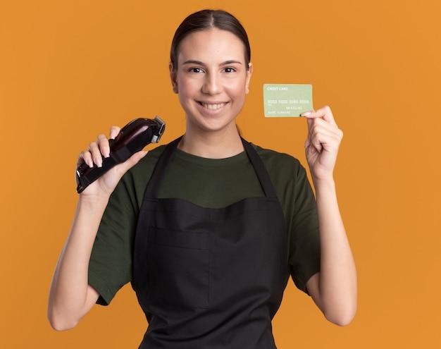 Lächelndes junges friseurmädchen in der uniform, die haarschneidemaschine und kreditkarte auf orange hält