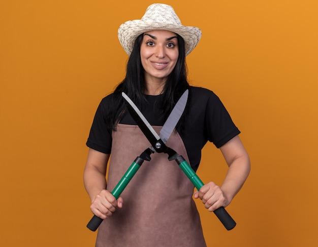 Lächelndes junges gärtnermädchen in uniform und hut mit heckenschere mit blick auf die vorderseite isoliert auf oranger wand