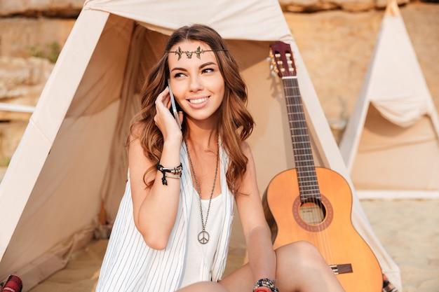Lächelndes junges hippie-mädchen, das beim sitzen am strandzelt am handy telefoniert