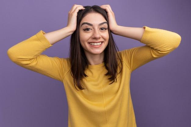 Lächelndes junges hübsches kaukasisches mädchen, das die hände auf dem kopf hält, isoliert auf lila wand