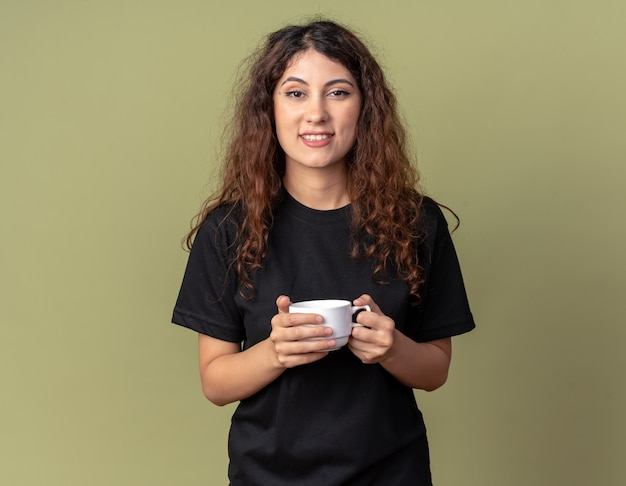Lächelndes junges hübsches kaukasisches mädchen, das eine tasse tee isoliert auf olivgrüner wand mit kopienraum hält
