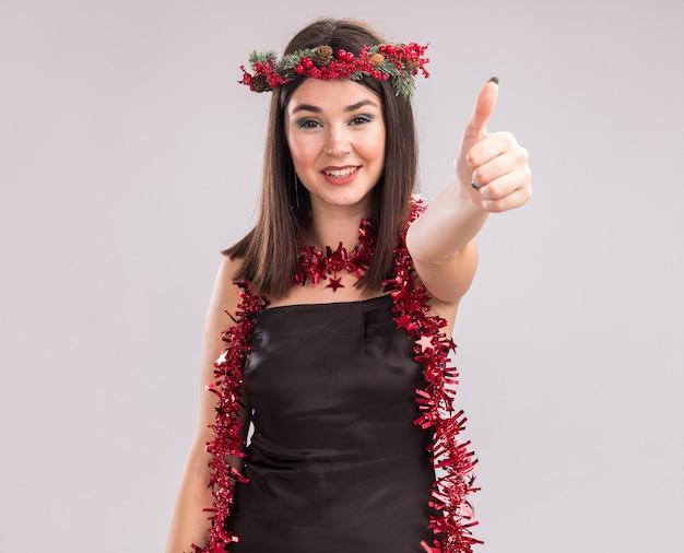 Lächelndes junges hübsches kaukasisches mädchen, das weihnachtskopfkranz und lametta-girlande um den hals trägt und in die kamera schaut, die den daumen einzeln auf weißem hintergrund mit kopienraum zeigt