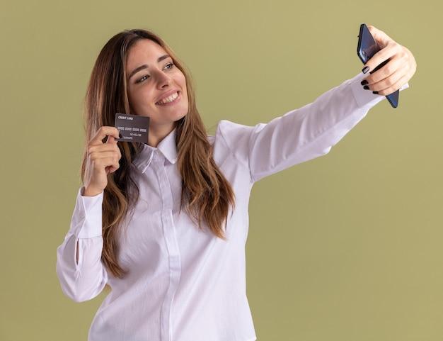 Lächelndes junges hübsches kaukasisches mädchen hält kreditkartenhalten und betrachtet telefon, das selfie auf olivgrün nimmt