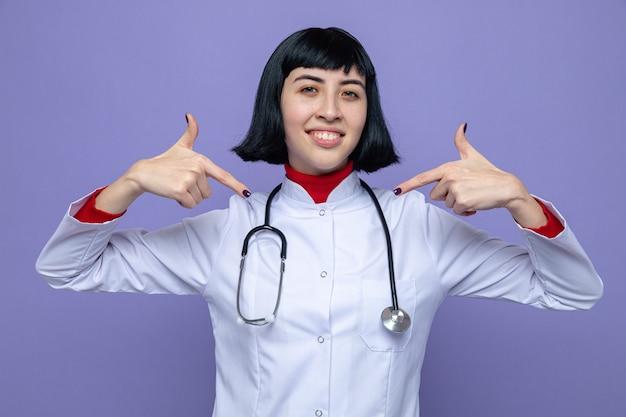 Lächelndes junges hübsches kaukasisches mädchen in arztuniform mit stethoskop, das auf sich selbst zeigt