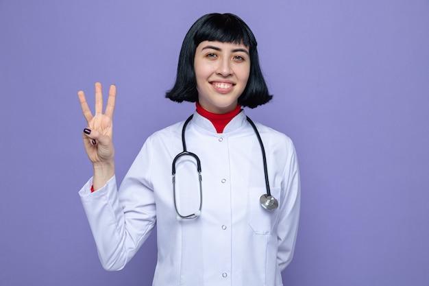 Lächelndes junges hübsches kaukasisches mädchen in arztuniform mit stethoskop, das drei mit den fingern gestikuliert