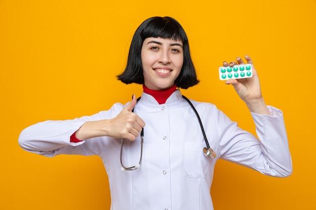 Lächelndes junges hübsches kaukasisches mädchen in arztuniform mit stethoskop, das pillenverpackung hält und nach oben greift
