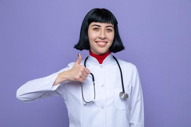 Lächelndes junges hübsches kaukasisches mädchen in der arztuniform mit dem stethoskop, das nach oben greift