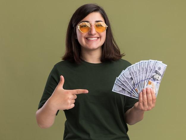Lächelndes junges hübsches kaukasisches mädchen in der sonnenbrille hält und zeigt auf geld, das kamera auf olivgrün betrachtet