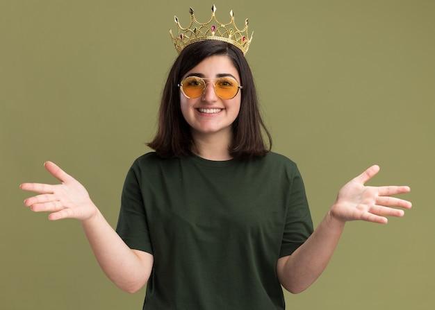 Lächelndes junges hübsches kaukasisches mädchen in der sonnenbrille mit der krone, die die hände offen hält