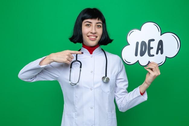 Lächelndes junges hübsches kaukasisches mädchen in doktoruniform mit stethoskop, das auf ideenblase hält und zeigt