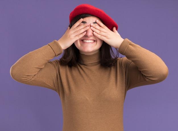 Lächelndes junges hübsches kaukasisches mädchen mit baskenmütze bedeckt die augen mit den händen, die auf purpurroter wand mit kopienraum isoliert sind