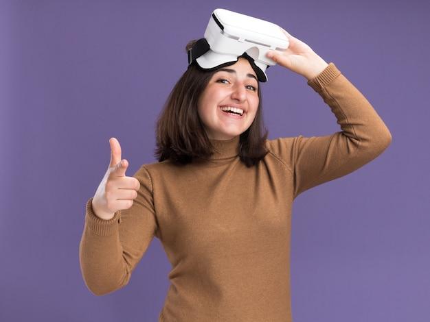 Lächelndes junges hübsches kaukasisches mädchen mit baskenmützenhut, der vr headset hält und auf kamera auf lila zeigt
