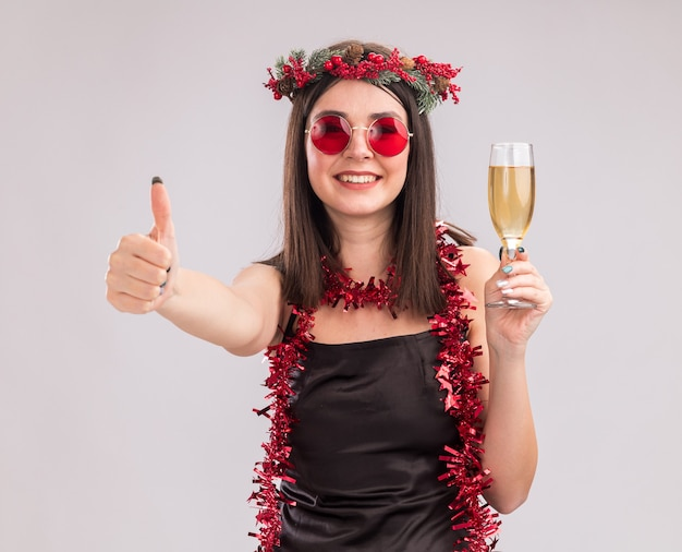 Lächelndes junges hübsches kaukasisches mädchen mit weihnachtskopfkranz und lametta-girlande um den hals mit brille, die ein glas champagner hält und in die kamera schaut, die den daumen einzeln auf weißem hintergrund zeigt