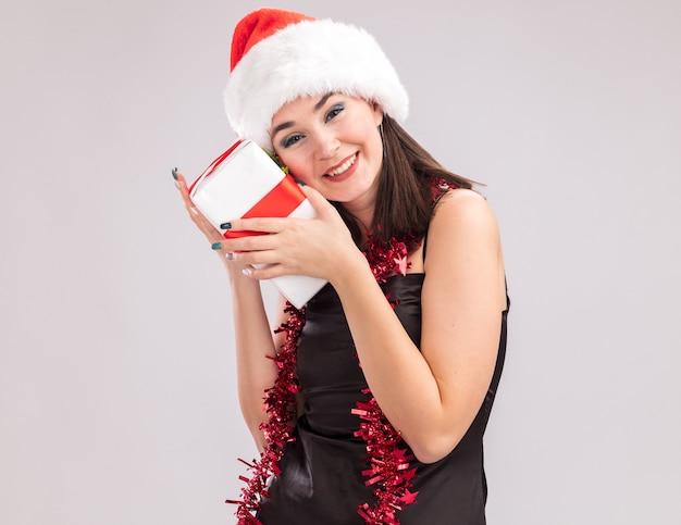 Lächelndes junges hübsches kaukasisches mädchen mit weihnachtsmütze und lametta-girlande um den hals, das in die kamera schaut, die ein geschenkpaket hält, das das gesicht berührt und dabei die kamera einzeln auf weißem hintergrund betrachtet