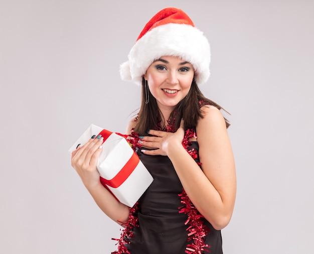 Lächelndes junges hübsches kaukasisches mädchen mit weihnachtsmütze und lametta-girlande um den hals, das in die kamera schaut, die ein geschenkpaket hält und die dankesgeste einzeln auf weißem hintergrund mit kopienraum tut