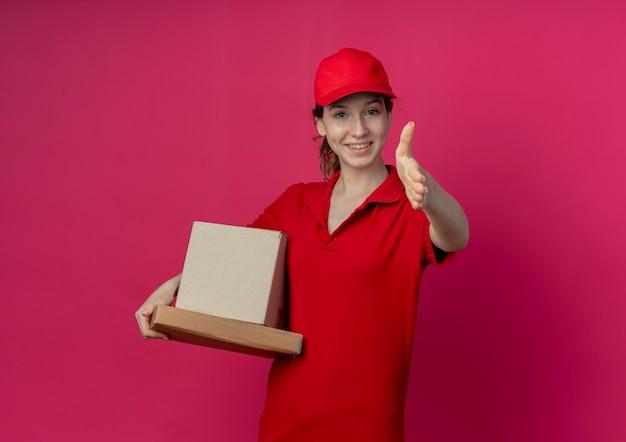 Lächelndes junges hübsches liefermädchen, das rote uniform und kappe hält, die pizzapaket und kartonschachtel ausstreckt, die hand in richtung kamera ausstreckt, die hallo lokalisiert auf purpurrotem hintergrund mit kopienraum gestikuliert